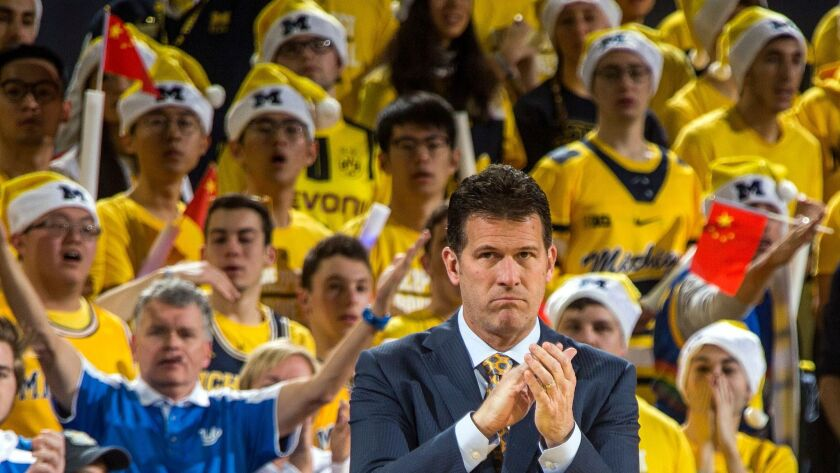 Michigan fans wave miniature Chinese flags behind UCLA coach Steve Alford during a Dec. 9 game.