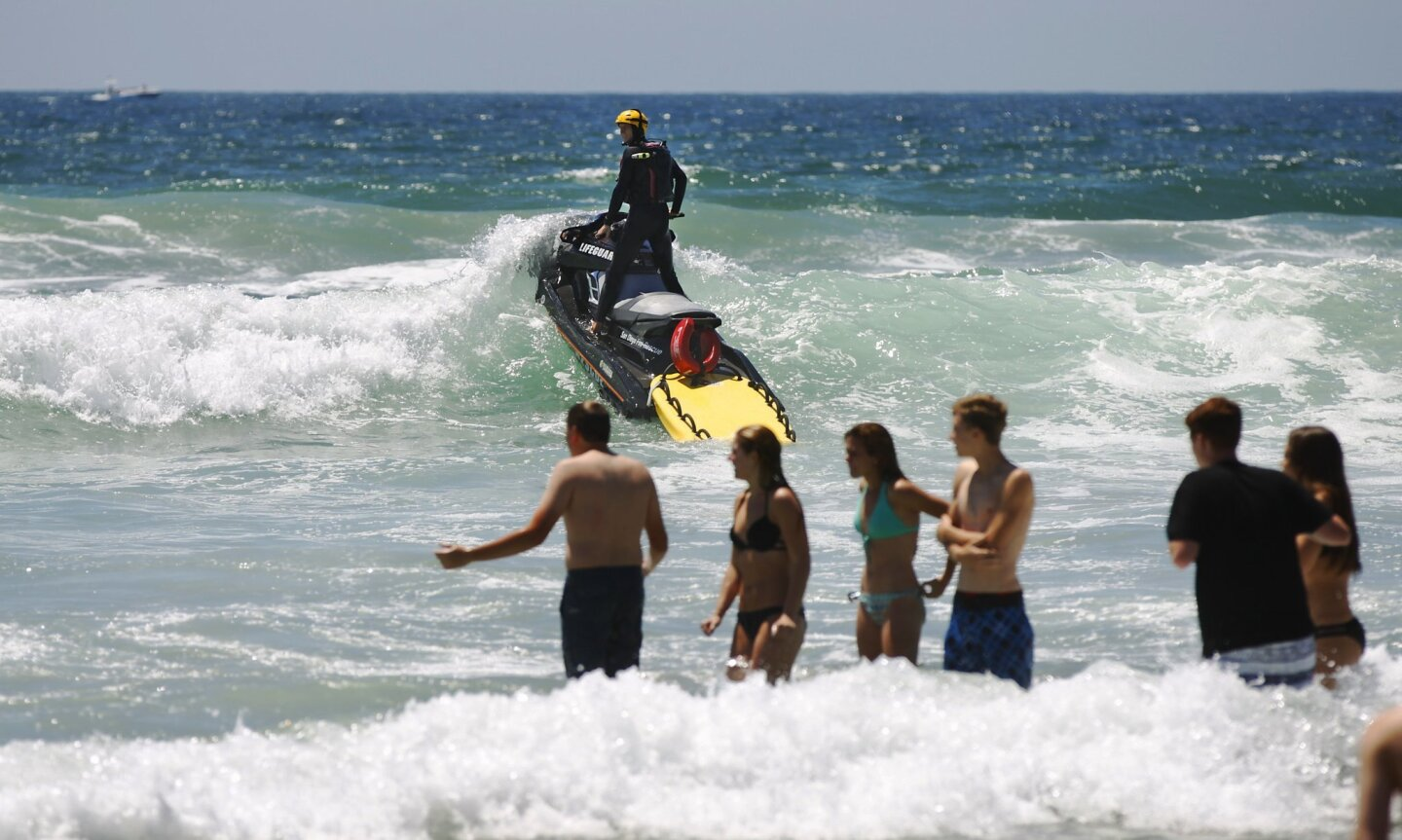 A San Diego Lifeguard patrols Mission Beach on a personal water craft. Strong rip currents, large surf and crowds flocking to the beach from record heat will make for a busy weekend at local beaches.