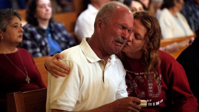 Jim Schettler cries during Mass at St. Rose Catholic Church in Santa Rosa. His daughter and her family lost their home in Fountaingrove and have moved in with Schettler and his wife.