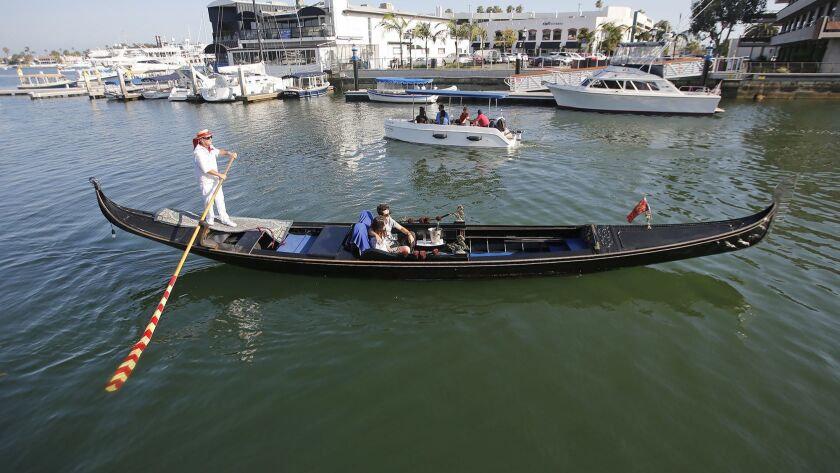 Co-owner Greg Lohr paddles a couple up Newport Bay on one of his Gondola Adventures boat on Friday.