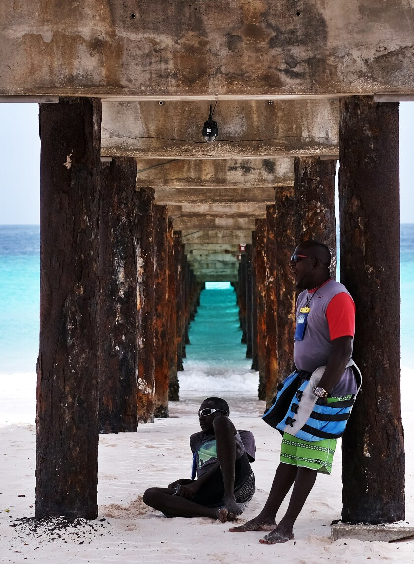 Two people stand under a jetty on a beach in Barbados.