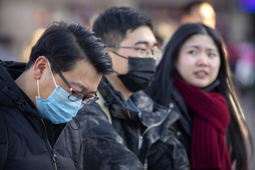 Travelers wear masks in Beijing, where anxiety rose after it was confirmed that the coronavirus can spread from human to human.
