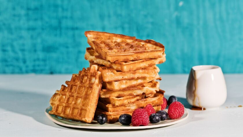 A stack of golden waffles, cut into triangles, on a plate with raspberries and blueberries, next to a container of syrup.