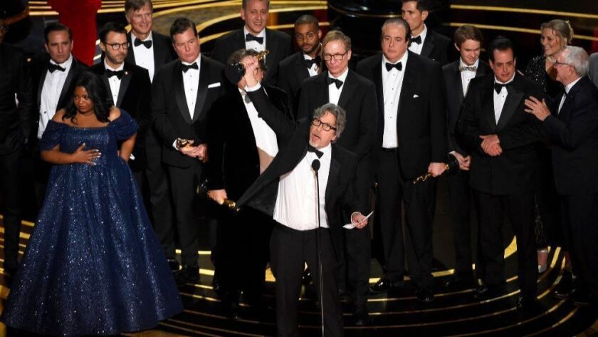 """Peter Farrelly, center, and the cast and crew of """"Green Book"""" accept the award for best picture at the Oscars on Feb. 24."""