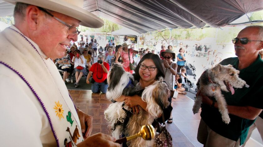 Monsignor Richard Duncanson, left, blesses two shitzu dogs during the annual Festival of the Bells at the Mission Basilica San Diego de Alcala.