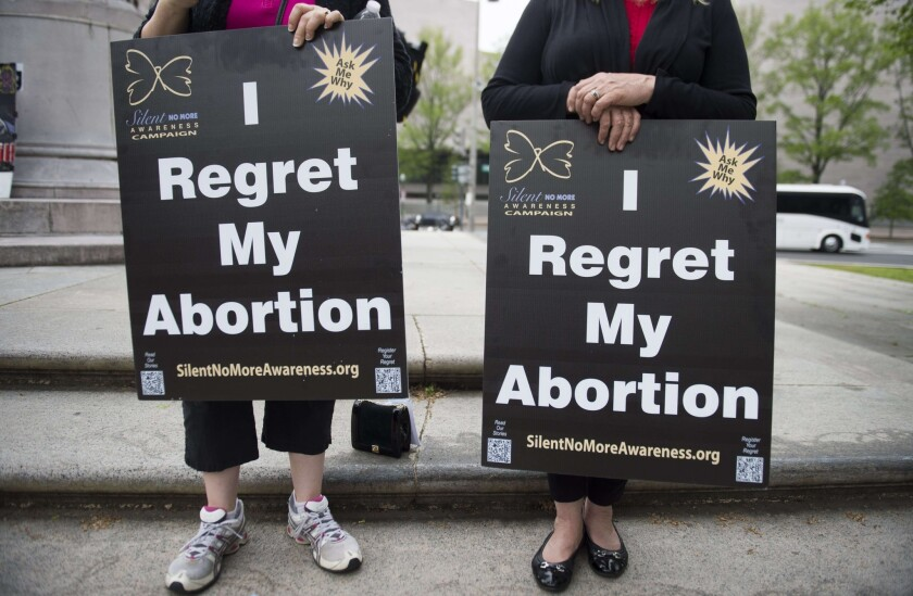 Anti-abortion demonstrators hold signs during a Priests for Life protest in Washington.