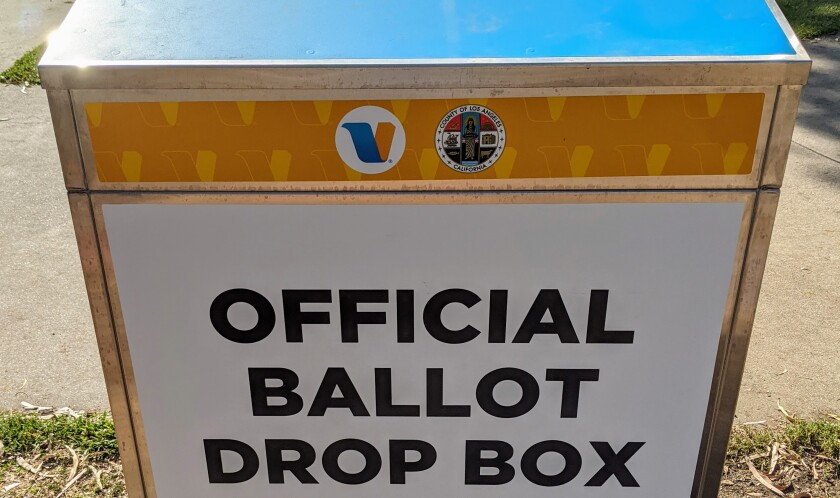 A sign that reads Official Ballot Drop Box on the front of a metal box
