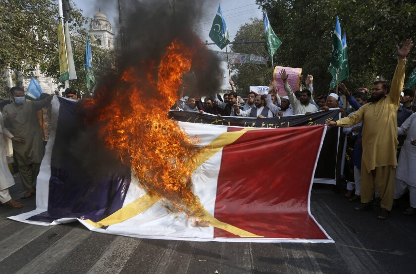 Supporters of religious group burn a representation of a French flag during a rally against French President Emmanuel Macron and republishing of caricatures of the Prophet Muhammad they deem blasphemous, in Lahore, Pakistan, Friday, Oct. 30, 2020. Muslims have been calling for both protests and a boycott of French goods in response to France's stance on caricatures of Islam's most revered prophet. (AP Photo/K.M. Chaudary)