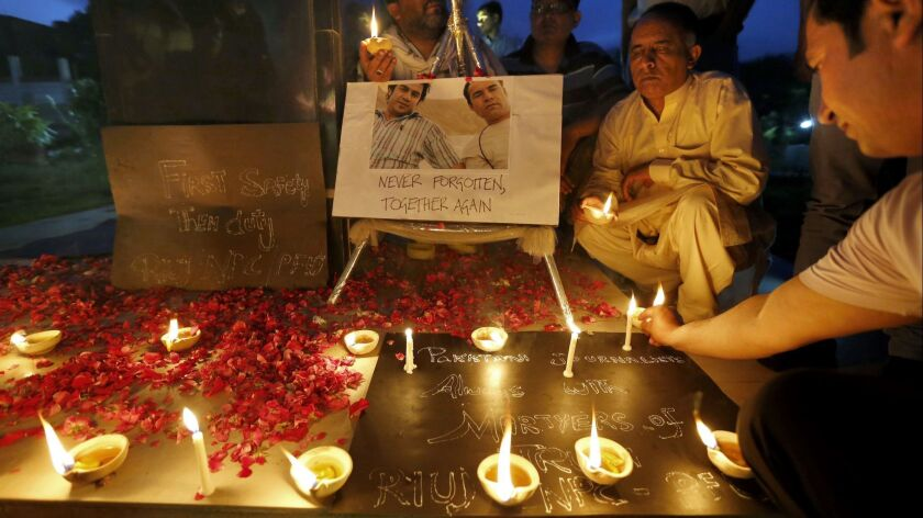 Members of the Pakistani media light clay-lamps and candles during a vigil Tuesday, May 1, 2018, in