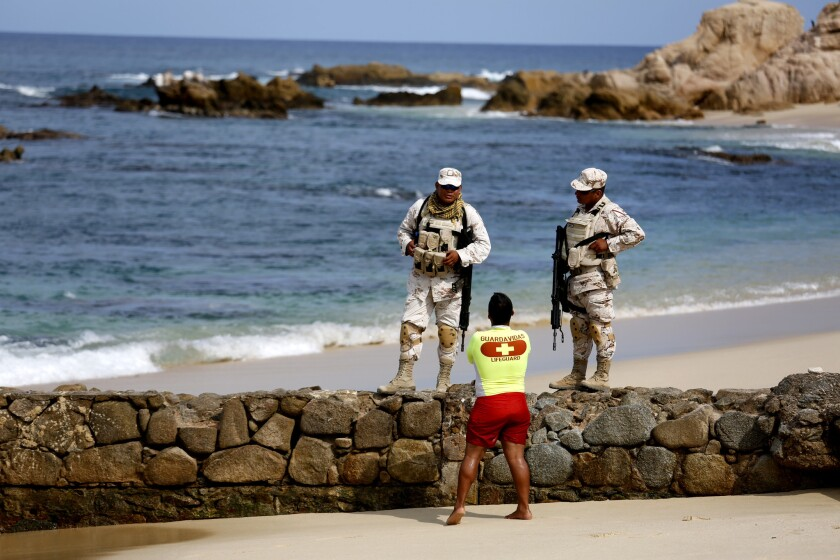 The Mexican Army patrols Palmilla Beach where recently three men were killed by a group of men with automatic weapons in San Jose del Cabo.