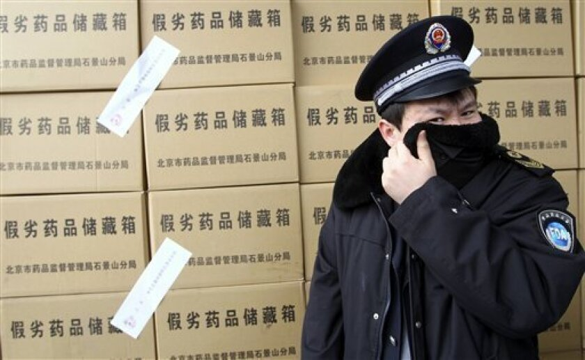 FILE - In this March 15, 2012 file photo, an official with the Food and Drug Administration covers his nose from the unpleasant smell from over 50 tons of confiscated fake medicine to be destroyed during a campaign to mark World Consumer Rights Day in Beijing, China. China's food and drug agency is defending itself against a media report alleging it's under investigation for corruption and doctoring inspection results. (AP Photo) CHINA OUT