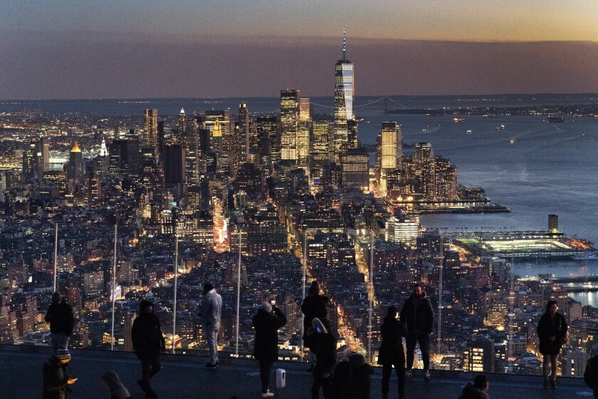 Visitors to the Edge, an outdoor observation deck 1100 feet above the ground, look at the lights of Manhattan, March 2, 2021, in New York. After the virus descended on New York, the only sounds in the streets were wailing ambulance sirens. A year after the pandemic began, the nation's largest metropolis -- with a lifeblood based on round-the-clock hustle and bustle, push and pull -- is adapting and showing new life. (AP Photo/Mark Lennihan)