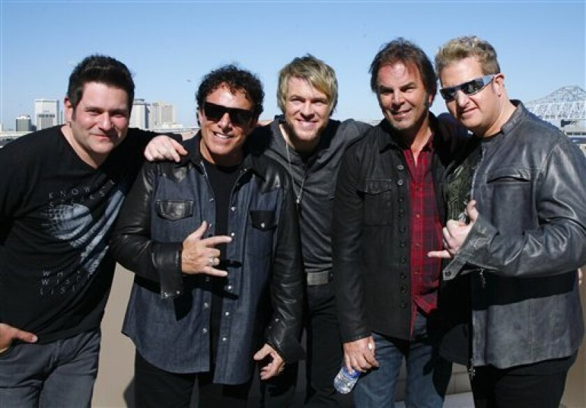 Journey's Jonathon Cain, left, and Neil Schon, second from left, pose with Rascal Flats Joe Dan Rooney, center, Jay DeMarcus and Gary Levox, right, in New Orleans Friday Feb. 1, 2013.  Journey and Rascal Flatts got on stage together for CMT's Crossroads concert Super Bowl weekend.  (AP Photo/ John