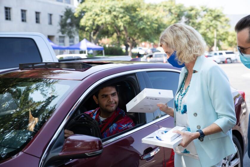 La presidenta de Cal State San Marcos, Ellen Neufeldt, entrega un iPad a un estudiante.