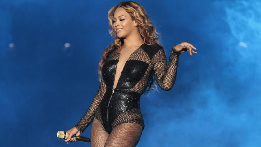 Beyoncé holds a microphone and smiles while wearing a black bodysuit
