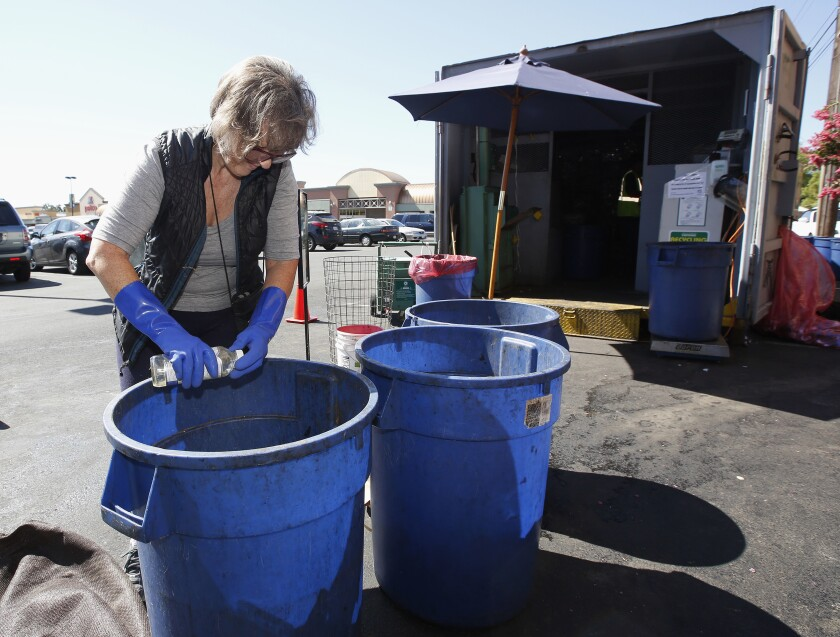 """FILE - In this Tuesday, July 5, 2016, file photo, Claudette Cole places a plastic bottle into a plastic container for recycling at a recycling center in Sacramento, Calif. Californians will have a better idea of what's headed for landfills instead of recycling centers under one of several related bills that Gov. Gavin Newsom signed into law Tuesday, Oct. 5, 2021. It sets the nation's strictest standards for which items can display the """"chasing arrows"""" recycling symbol, advocates say. (AP Photo/Rich Pedroncelli, File)"""