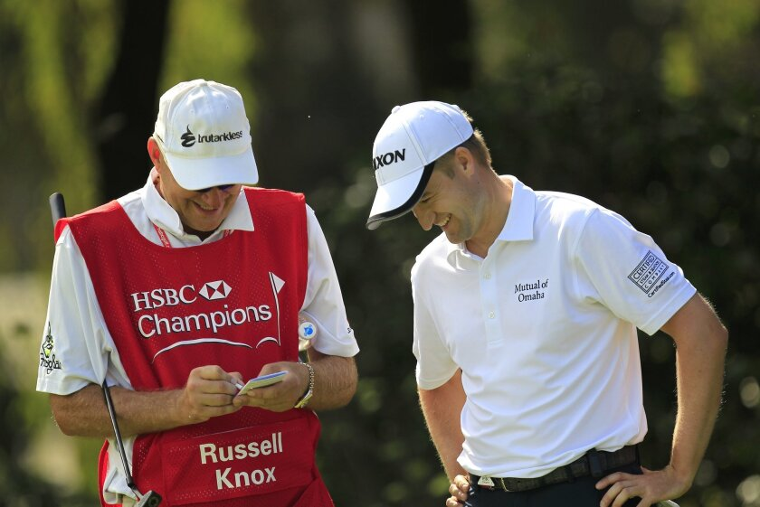 Russell Knox of Scotland, right, smiles with his caddy on the 6th hole during the second round of the HSBC Champions golf tournament at the Sheshan International Golf Club in Shanghai, China Friday, Nov. 6, 2015. (AP Photo)