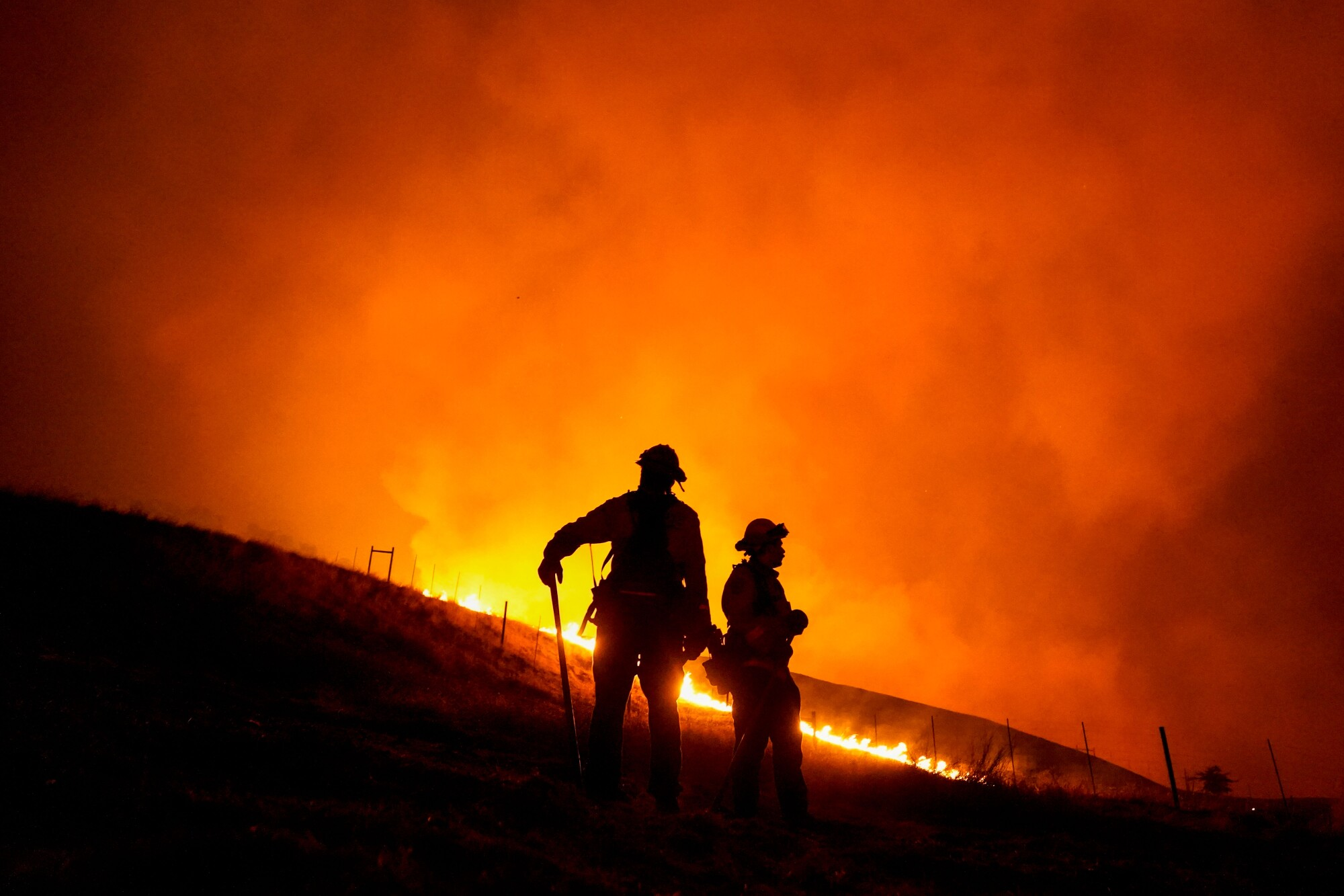 Members of the Santa Rosa Fire Department stand before a hill in flames.