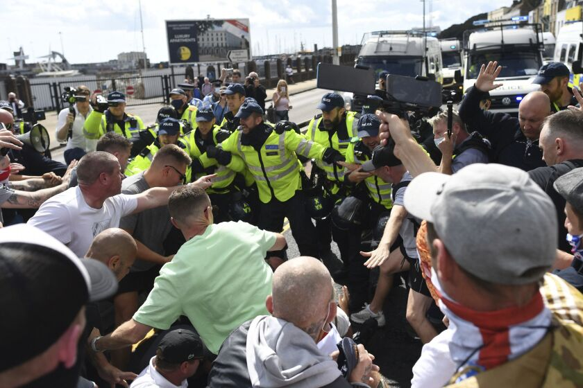 Anti-migrant protesters react with police, in Dover, England, Saturday, Sept. 5, 2020. Police controlled a small scale demonstration against immigration, calling for authorities to do more to protect English shores, at England's southern port city nearest to mainland Europe. (Stefan Rousseau/PAvia AP)