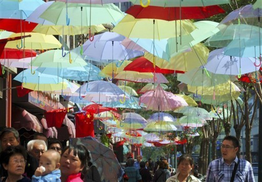 In this Tuesday, Sept. 3, 2013 photo, people walk through a commercial street decorated with colorful umbrellas in Shenyang in northeast China's Liaoning province. China's August export growth accelerated, adding to signs of a gradual recovery for the world's second-largest economy, while import growth weakened. Exports rose 7.2 percent to $190.7 billion, accelerating from July's 5.1 percent growth, customs data showed Sunday. Imports rose 7 percent to $162.1 billion, but that was down from July