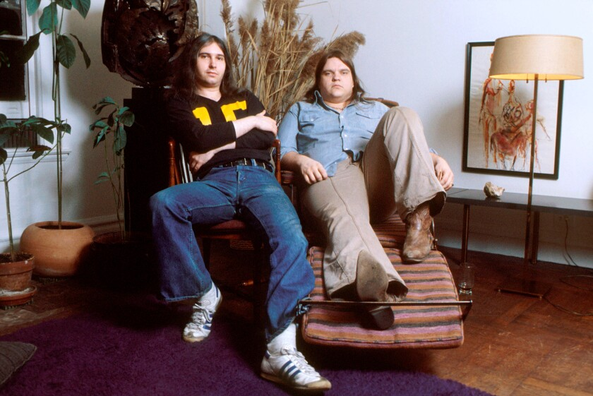 Jim Steinman and Meat Loaf pose for a photo seated.