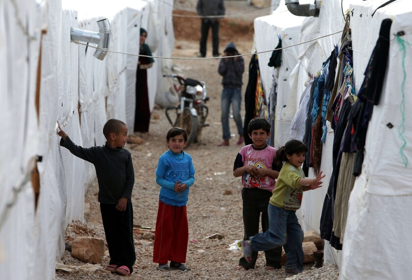 Syrian children play outside their tents at a refugee camp in the city of Arsal in Lebanon's Bekaa valley on March 28, 2014. The city has been a focal point of sectarian strife, a spillover from the civil war in Syria.