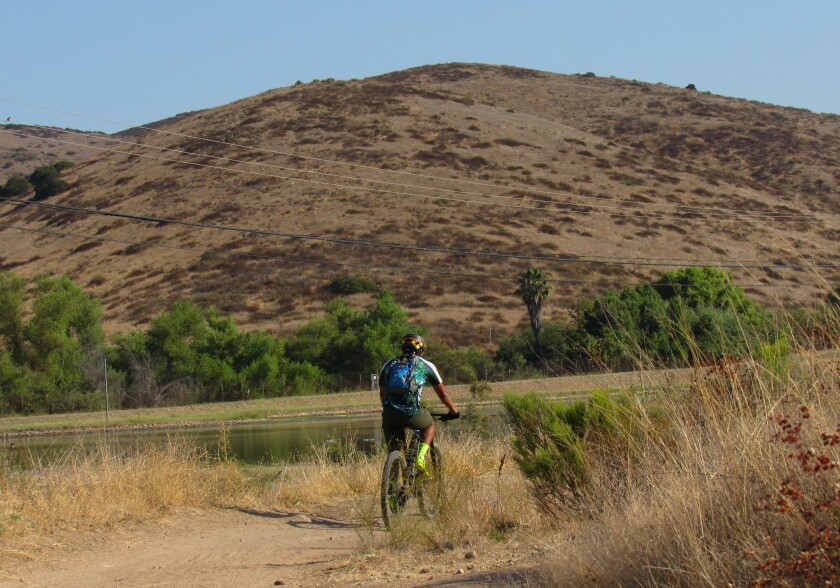 A cyclist moves along a trail Sunday morning on property in Fanita Ranch, the planned housing development in Santee.