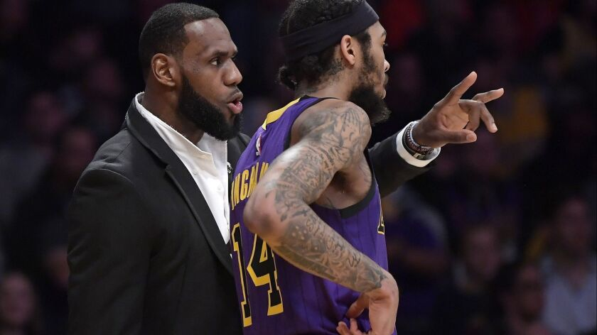 Injured forward LeBron James talks to Lakers teammate Brandon Ingram during the second half of the game against Knicks on Friday,.