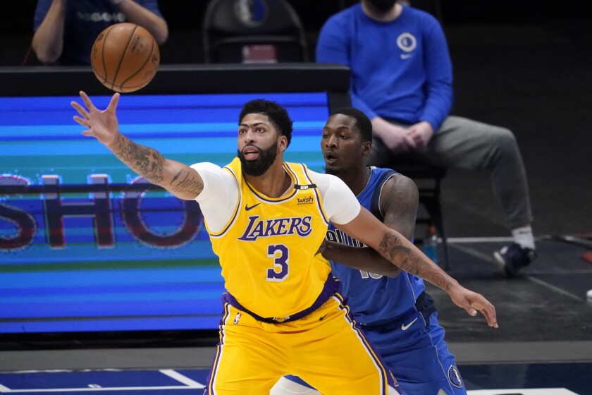 Lakers' Anthony Davis reaches out for a pass as Dallas Mavericks' Dorian Finney-Smith defends.