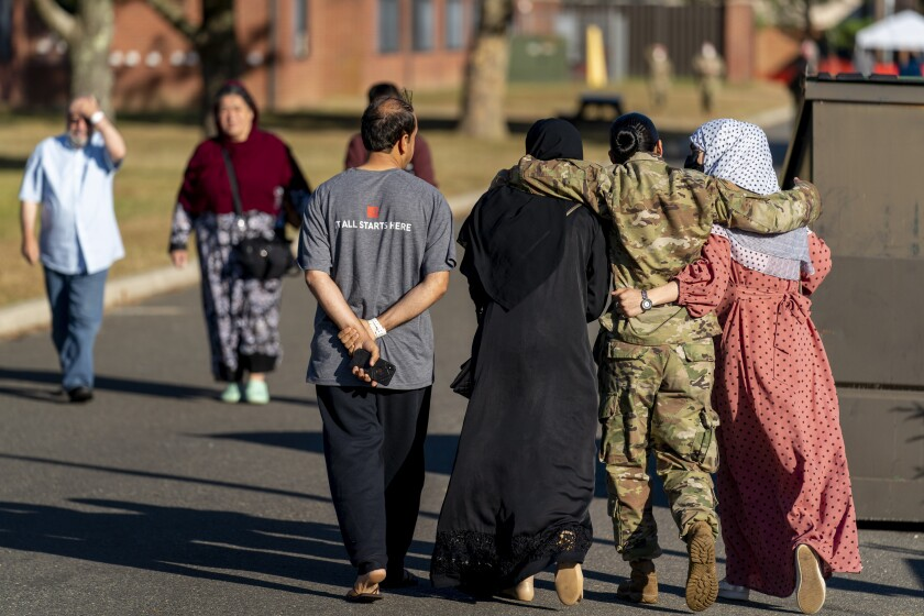 A member of the military puts her arms around two female Afghan refugees at a refugee camp on Sept. 21 in Lakehurst, N.J.