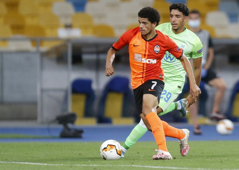 Shakhtar's Taison, front, duels for the ball with Wolfsburg's Omar Marmoush during the Europa League round of 16 second leg soccer match between FC Shakhtar Donetsk and VfL Wolfsburg at the Olimpiyskiy Stadium in Kyiv, Ukraine, Wednesday, Aug. 5, 2020. (AP Photo/Efrem Lukatsky)