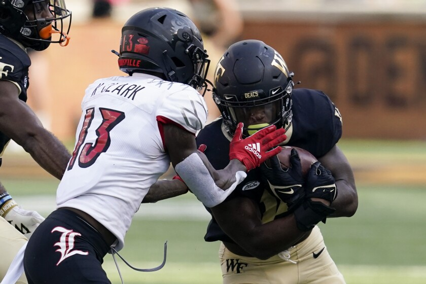 Wake Forest running back Justice Ellison is tackled by Louisville defensive back Kei'Trel Clark during the second half of an NCAA college football game on Saturday, Oct. 2, 2021, in Winston-Salem, N.C. (AP Photo/Chris Carlson)
