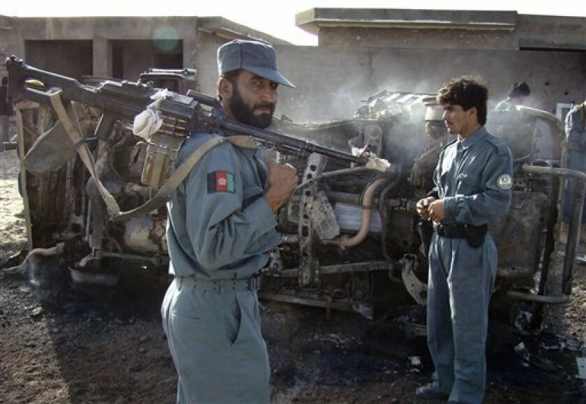 In this photo taken Saturday, July 4, 2009, an Afghan police officer carries his gun on his shoulder, as a destroyed vehicle is seen in the background following a suicide attack in Lashkar Gah, the provincial capital of Helmand province south of Kabul, Afghanistan. An Afghan civilian was killed and five others were wounded in the attack, Afghan police officials said. (AP Photo/Abdul Khaleq)