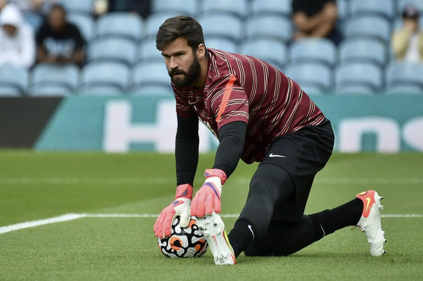 Liverpool's goalkeeper Alisson stretches during warmup before the English Premier League soccer match between Leeds United and Liverpool at Elland Road, Leeds, England, Sunday, Sept. 12, 2021. (AP Photo/Rui Vieira)