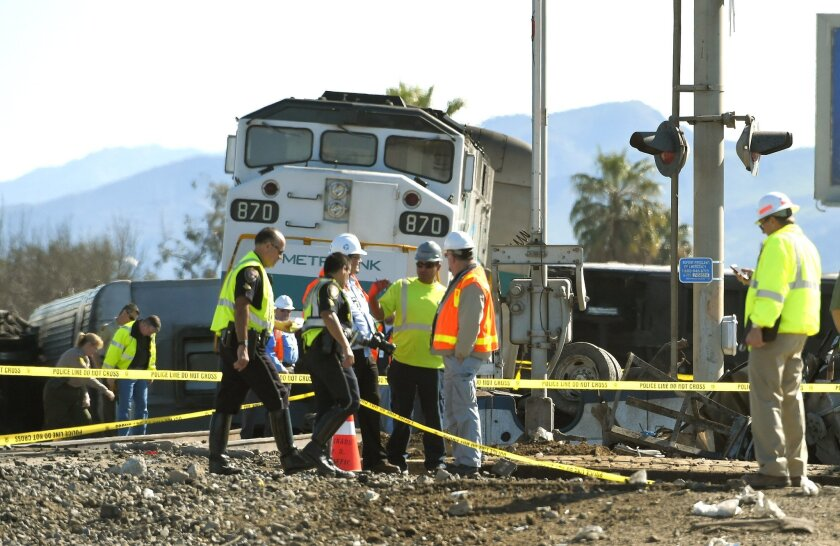 In this Tuesday, Feb. 24, 2015, file photo, Workers stand near a Metrolink train that hit a truck and then derailed in Oxnard, Calif. Three cars of the Metrolink train tumbled onto their sides, injuring dozens of people in the town 65 miles northwest of Los Angeles. Engineers have figured how to blunt the deadly force of a train smashing into a truck on the tracks. Yet few U.S. rail systems have adopted the technology, which is believed to have played a significant role in the remarkably low number of serious injuries from Tuesday's commuter rail crash in California. (AP Photo/Mark J. Terrill, File)