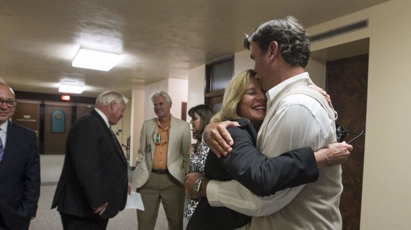 Rita Brandin, of Newland Communities, gets a hug in the hallway after the San Diego County Board of Supervisors voted 4-0 last month to approve the controversial Newland Sierra housing project in North County.