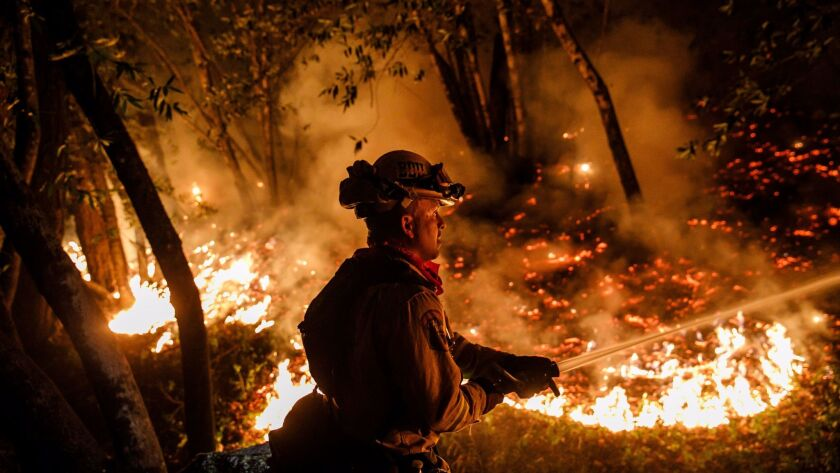 Cal Fire firefighter Mario Topete sprays water to help prevent flames from crossing Highway 29, north of Calistoga, on Thursday.