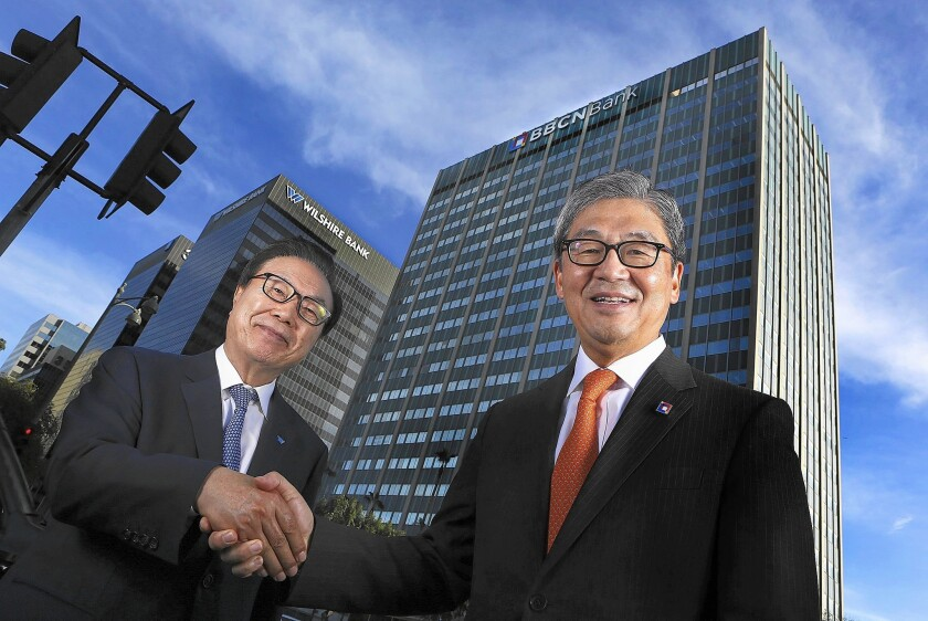 Steven Koh, left, chairman of Wilshire Bancorp, and Kevin Kim, BBCN Bancorp's chairman and CEO, shake hands in December.