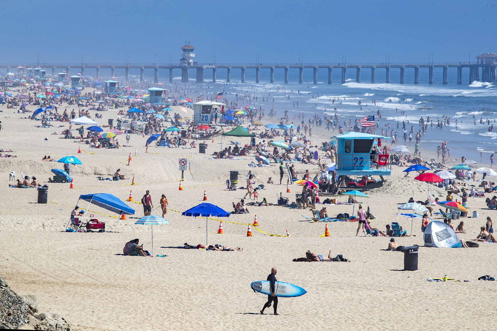 Thousands of beachgoers enjoyed a warm, sunny day at Huntington Beach despite state-mandated stay-at-home orders.
