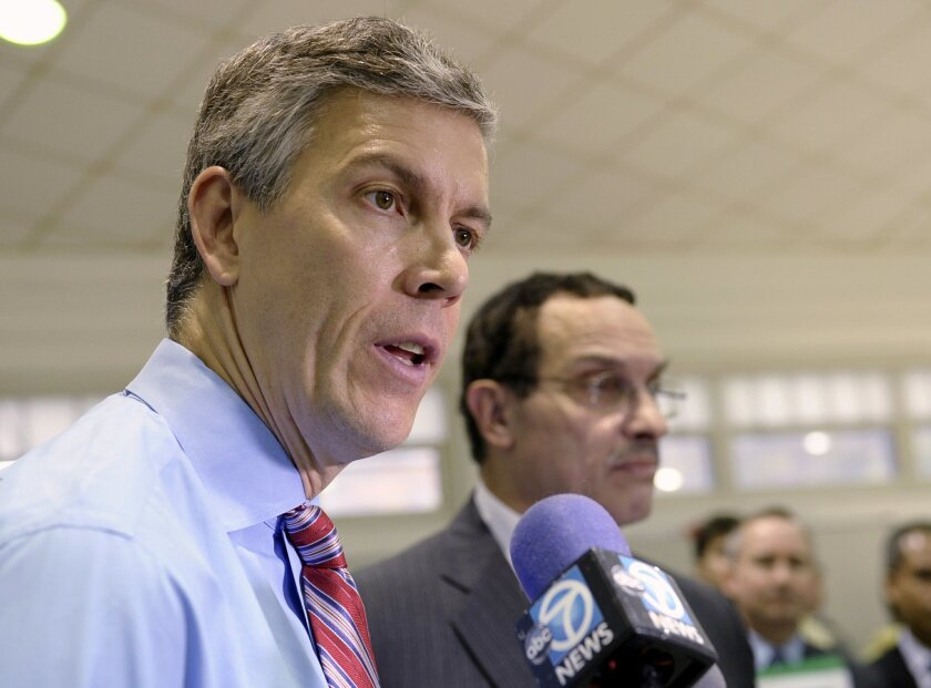 FILE - In this Nov. 7, 2013 file photo, Education Secretary Arne Duncan, left, speaks to reporters at Malcolm X Elementary School in Washington. Critics are relentless in warning about what they see as the folly of the new Common Core academic standards. The standards were written in private and ne