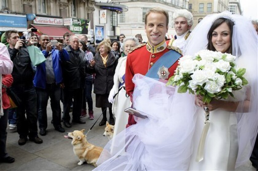 Impersonators Simon Watkinson as Prince William, left, and Jodie Bredo as Kate Middleton, right, walk through the streets of London in wedding attire to promote photographer Alison Jackson's new book 'Kate and Wills Up The Aisle'. Friday, April 1, 2011. Jackson became well known in 1999 with her look alike photographs of celebrities in compromising positions. (AP Photo/Jonathan Short)