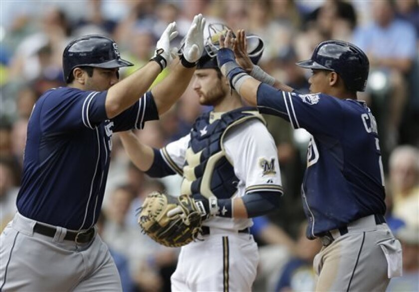 San Diego Padres' Carlos Quentin, left, and Everth Cabrera celebrate after Quentin's two-run home run against the Milwaukee Brewers during the third inning of a baseball game Thursday, July 25, 2013, in Milwaukee. In the background is Brewers catcher Jonathan Lucroy. (AP Photo/Jeffrey Phelps)
