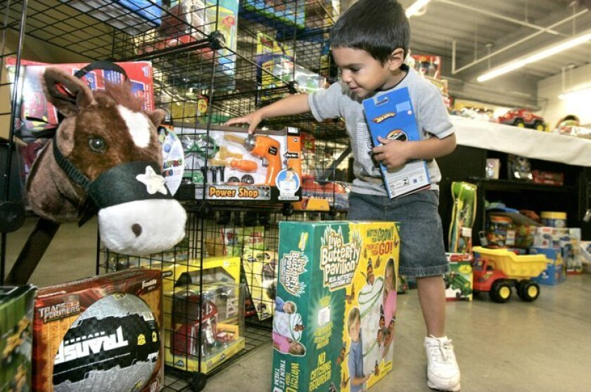 Jordan Mortazi, 3, picked out a toy at the Del Mar Fairgrounds during the annual Christmas Basket program run by the Community Resource Center. The center's director said youth groups in schools had broken all records in gathering food for the program this year.
