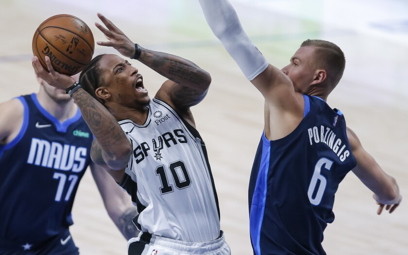San Antonio Spurs forward DeMar DeRozan (10) prepares to shoot as Dallas Mavericks forward Kristaps Porzingis (6) defends during the first half of an NBA basketball game Wednesday, March 10, 2021, in Dallas. (AP Photo/Brandon Wade)