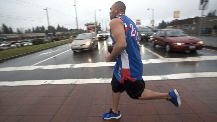 Lamont Thomas runs in Shoreline, Wash., dressed in one of the vintage basketball jerseys he collects.