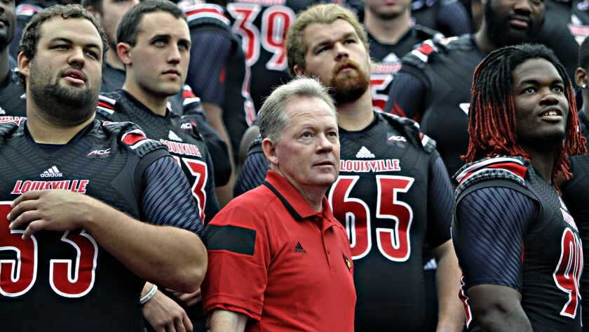 Louisville Coach Bobby Petrino looks on with his players during the team's picture day on Aug. 9. Louisville is the latest team to join the Atlantic Coast Conference.