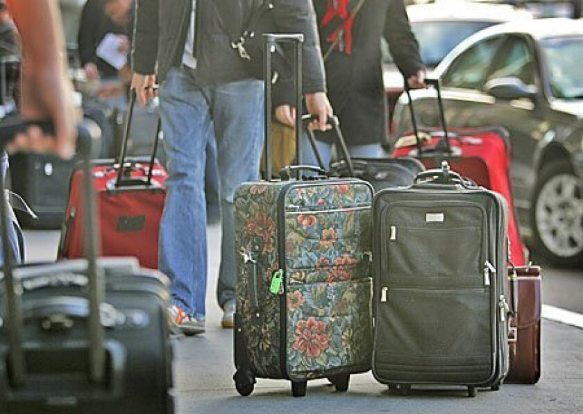 The San Diego City Council accepts a report calling for a massive makeover of Lindbergh Field, even as some council members raise questions about traffic and parking issues tied to the proposal. Above, passengers at Lindbergh Field roll their bags to Terminal 2.