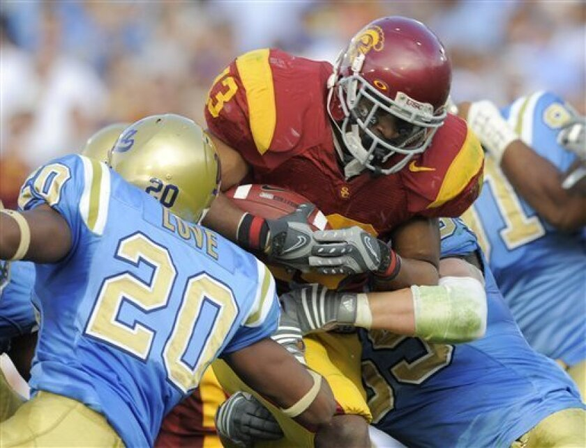 Southern California running back Stafon Johnson scores between UCLA safety Glenn Love, left, and cornerback Lowell Rose during the first half of an NCAA college football game at the Rose Bowl in Pasadena, Calif., Saturday, Dec. 6, 2008. (AP Photo/Chris Carlson)