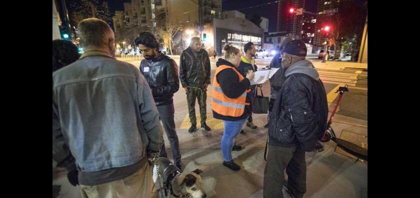 Volunteers conduct point-in-time surveys with homeless people at the corner of Park Boulevard and J. Street, in East Village, during the annual homeless count, before sunrise Jan. 25.