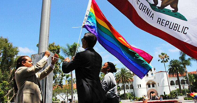 San Diego State students, faculty and staff raise the rainbow flag, a symbol of LGBT pride, during a ceremony on campus.